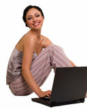 Casual woman on laptop. Attractive short hair brunette wearing pajamas sitting on white with laptop laughing expression Stock Photography