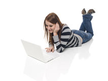 Casual Woman - Laptop. Isolate studio shot of a casually dressed, happy young adult woman working on a laptop computer while laying down Stock Photo