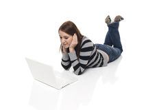 Casual Woman - Laptop. Isolated studio shot of a casually dressed young adult woman working on a laptop computer while laying down Royalty Free Stock Photo