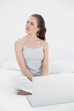 Casual woman with laptop looking to her side in bed. Casual young woman with laptop looking to her side in bed at home Royalty Free Stock Images