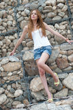 Casual woman leaning on a huge rock wall Royalty Free Stock Photo