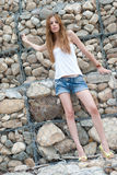 Casual woman leaning on a huge rock wall Stock Photography