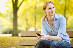 Casual Woman Listening to Music in a Park Stock Photo