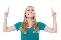 Casual woman looking and pointing upwards Royalty Free Stock Images