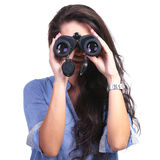 Casual woman looks at you through binoculars. Closeup of a young casual woman looking into the camera through binoculars. on white background Royalty Free Stock Photography