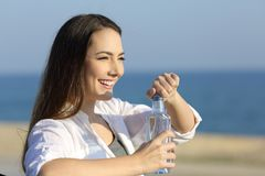 Casual woman opening a water bottle on the beach Stock Photo