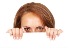 Casual woman peeping over a billboard Royalty Free Stock Photos