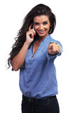 Casual woman points at you while on the phone Royalty Free Stock Images