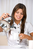 Casual woman pouring coffee Royalty Free Stock Image