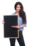 Casual woman presents something on her blackboard Stock Photography