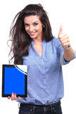 Casual woman presents tablet and shows thumb up Royalty Free Stock Photos