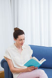 Casual woman reading on the couch Royalty Free Stock Photo