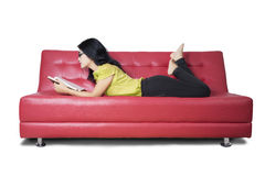 Casual woman reads a novel on sofa Royalty Free Stock Images