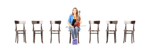 Casual woman seated on a chair holding a violin and waiting for Royalty Free Stock Images