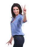 Casual woman shows victory sign Royalty Free Stock Images