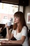 Casual woman sipping coffee in cafe Royalty Free Stock Image