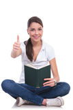 Casual woman sits with book & ok Stock Images