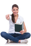 Casual woman sits with book & points Royalty Free Stock Photo