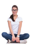 Casual woman sits on ground Royalty Free Stock Images