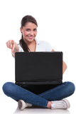 Casual woman sits with laptop & points Royalty Free Stock Photography