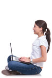 Casual woman sits with laptop Stock Image