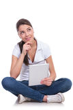 Casual woman sits pensive with pad Royalty Free Stock Photography