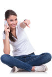 Casual woman sits & points on phone Stock Photography