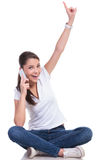 Casual woman sits & points & talks. Casual young woman sitting with legs crossed and talking on the phone while pointing upwards and looking at the camera with a Stock Image