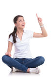 Casual woman sits & points up Royalty Free Stock Photos