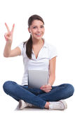 Casual woman sits & victory & pad Royalty Free Stock Image