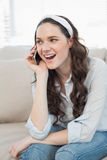 Casual woman sitting on a cosy couch having a phone call Stock Photos