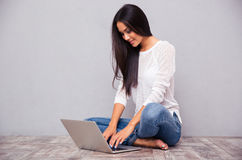 Casual woman sitting on the floor with laptop Stock Photos