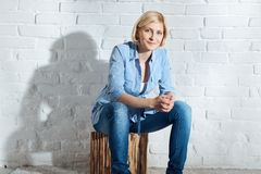 Casual woman sitting front of white brick wall Stock Photo