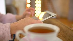 Casual woman sitting inside a coffee shop. Woman using tablet at a cafe with cofee or tea. close-up. Young people using. Casual woman sitting inside a coffee stock footage