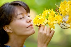 Casual woman smelling flowers Stock Photo