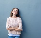 Casual woman smiling with arms crossed on gray background Stock Images