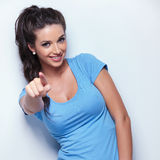 Casual woman smiling and pointing her finger Stock Images