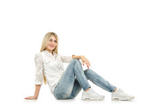 Casual woman smiling sitting on the floor - isolated over a whit Royalty Free Stock Image