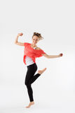 Casual woman, student jumping. Isolated on grey. Stock Image