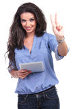 Casual woman with tablet shows victory Royalty Free Stock Photos