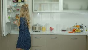Casual woman taking food ingredients out of fridge