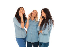3 casual woman talking on the phone and looking up. 3 casual women talking on the phone and looking up to something on white studio background Royalty Free Stock Photography