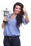 Casual woman with trophy shows thumb up Royalty Free Stock Images