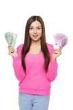 Casual woman with us dollars abd euro cash. Surprised young woman in bright pink sweater holding us dollar money in one hand and euro cash money in another hand Stock Photo