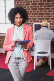 Casual woman using digital tablet with colleague behind in office. Young casual women using digital tablet with colleague behind in the office Royalty Free Stock Image