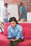 Casual woman using digital tablet on couch Royalty Free Stock Photography