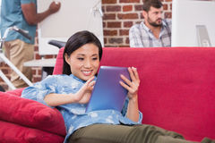 Casual woman using digital tablet on couch Royalty Free Stock Image