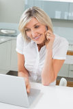 Casual woman using laptop while on call in kitchen Royalty Free Stock Photo