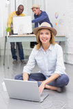 Casual woman using laptop with colleagues behind in office Royalty Free Stock Photography