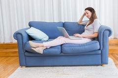 Casual woman using laptop on couch Royalty Free Stock Photography